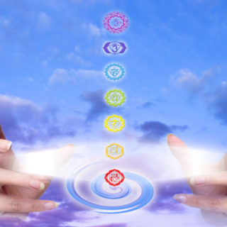 hands with rays of light and seven chakra like a concept of healing hands